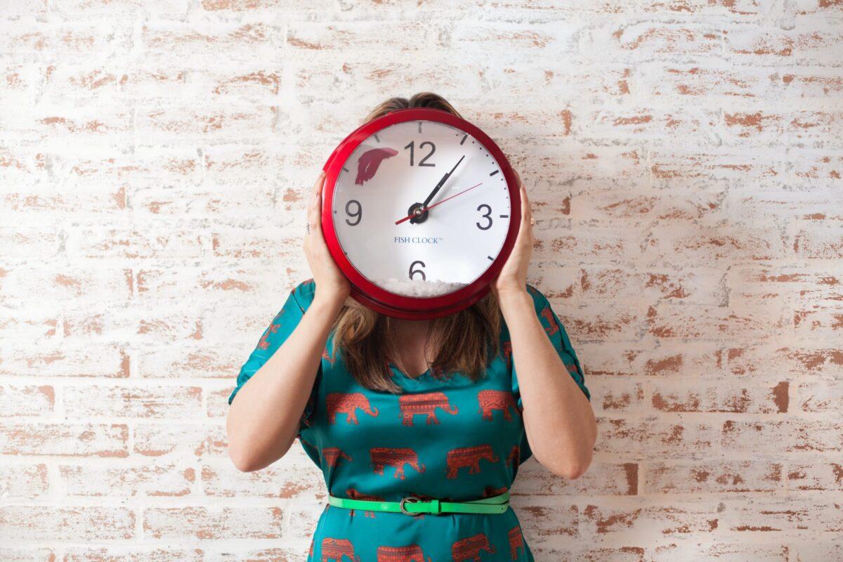 Mulher segurando relógio.