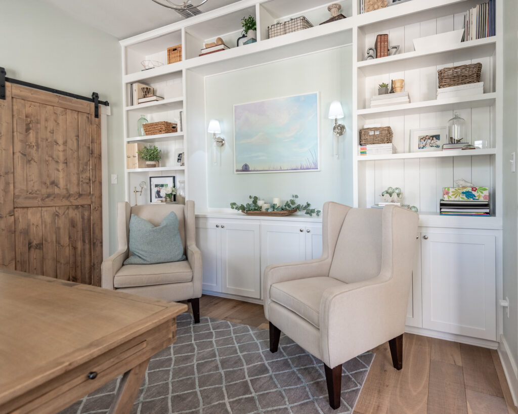 A home office with built in bookshelves 2 chair and a desk, the paint color is Sherwin Williams Sea Salt