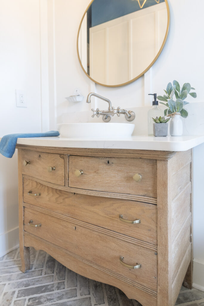 This money saving option is to recycle and repurpose: a bathroom vanity made from an antique wood dresser. It has a white quartz counter and vessel sink.