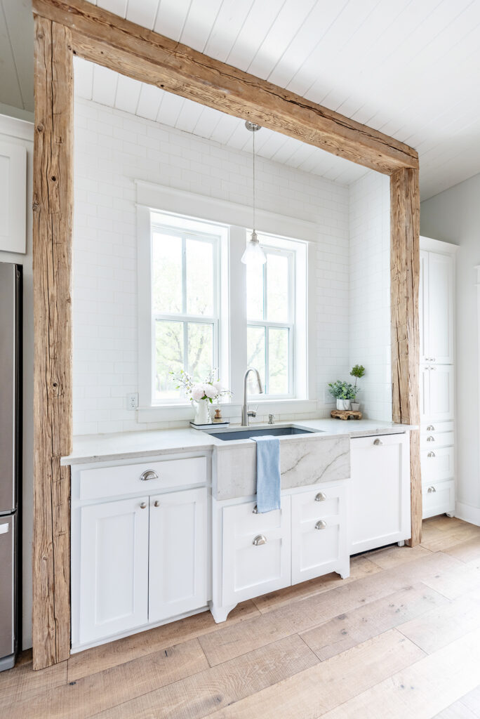 A charming kitchen view of a European farmhouse sink surrounded by white subway tile and reclaimed wood beams and columns. There are 2 windows above the sink and a blue towel draped over the edge.