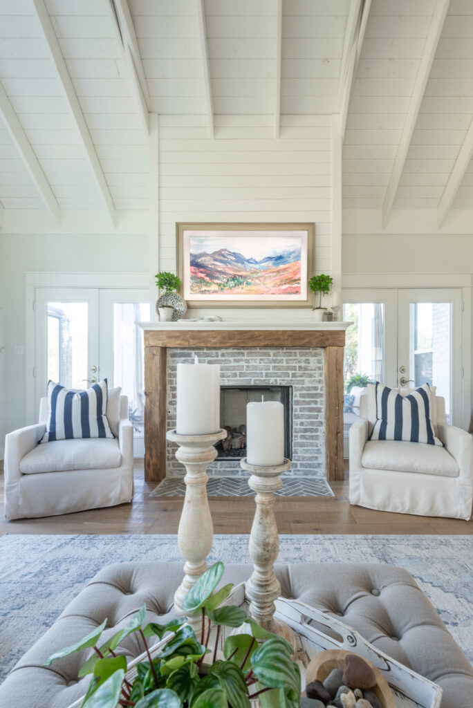 A living room with vaulted ceilings and exposed rafters. There is a fireplace centered in the room with gray brick an reclaimed wood surround, flanked by 2 white chairs, the tv is disguised as a painting above the fireplace