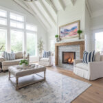 a view of a vaulted living room with large windows facing out the back and french doors going to a screened porch