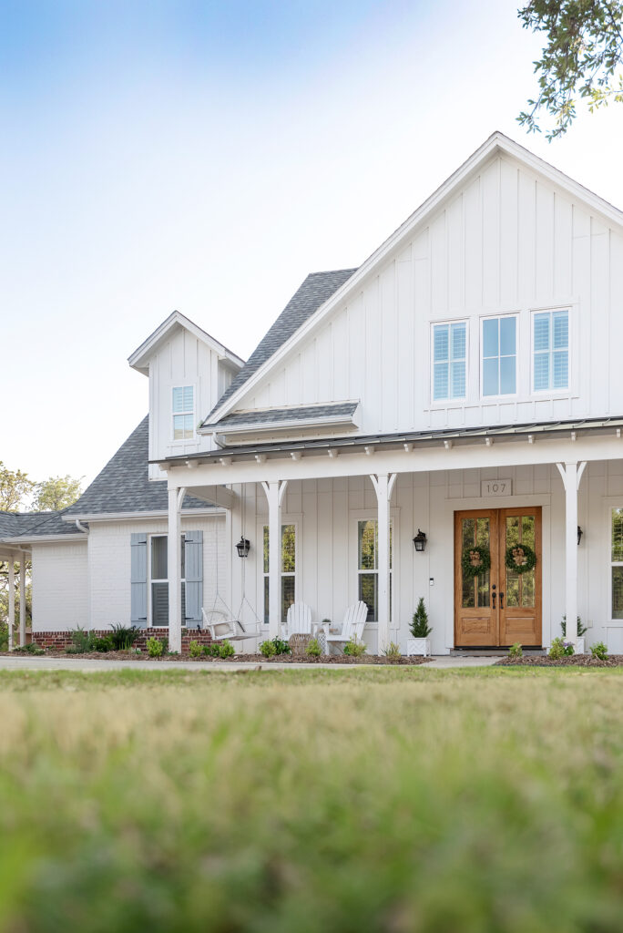A white farmhouse with a wide front porch, a double front door, and large gable.