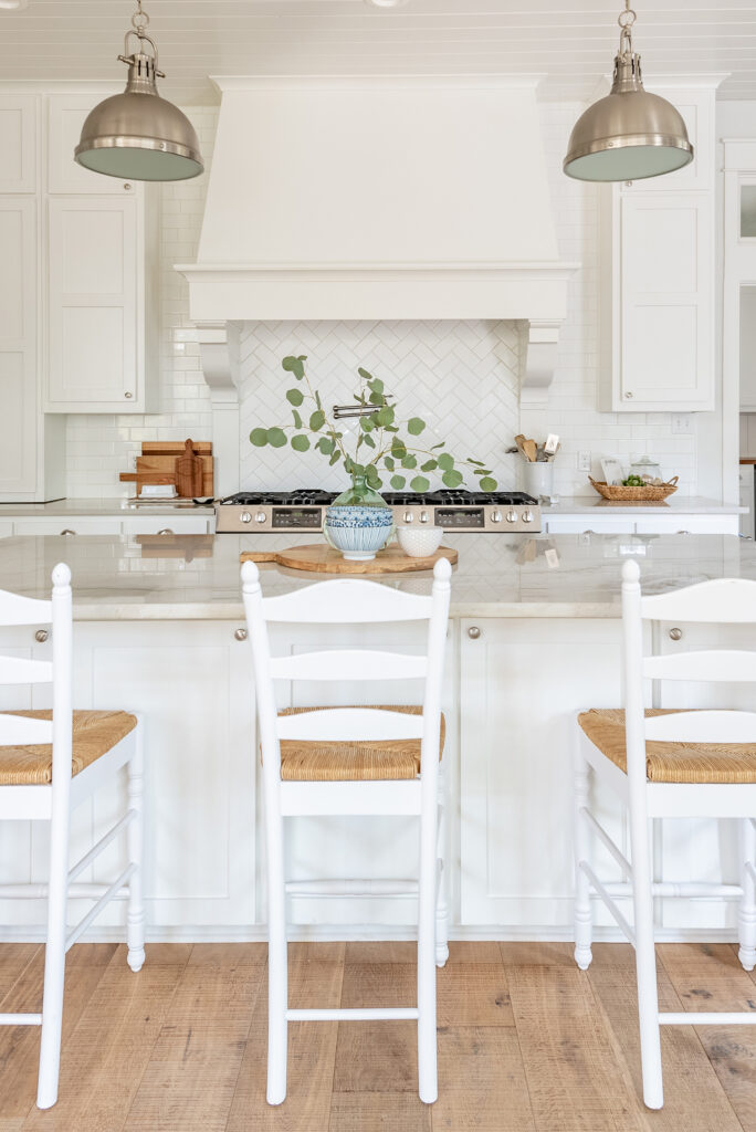 a view of a white farmhouse kitchen with island and barstools
