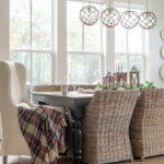 plaid fall blanks hangs over an upholstered dining chair at a farmhouse table
