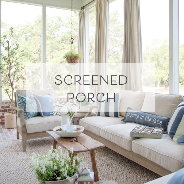 a screen porch with a fireplace, drop cloth curtains, and outdoor furniture