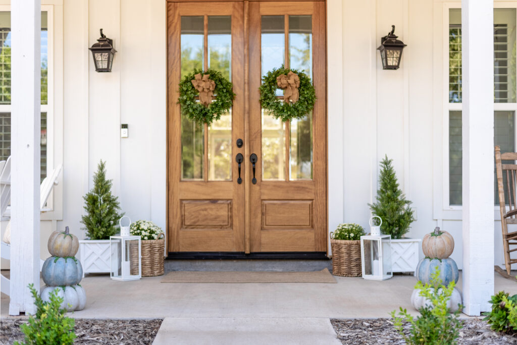 Front Porch of a white Farmhouse with double wood doors holding green boxwood wreaths with burlap bows. The porch is decorated for Fall. There are stacked pumpkins, and baskets holding mums and lanterns