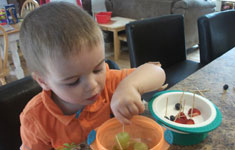 Boy eating from orange bowl