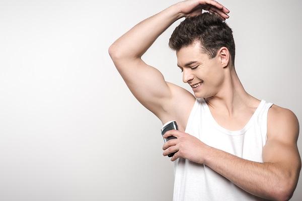 smiling man in white sleeveless shirt applying deodorant on underarm isolated on grey