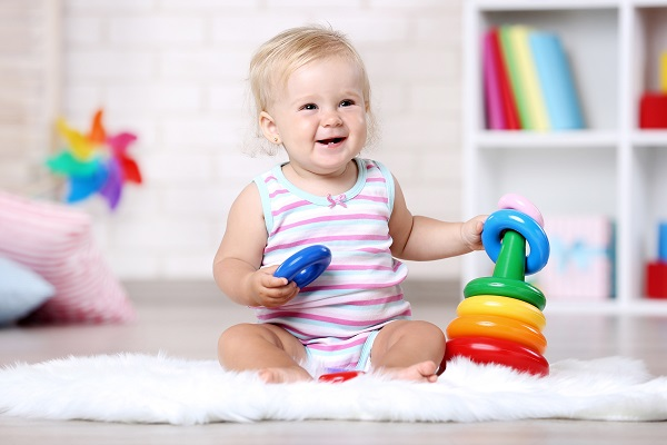 Baby girl sitting on white carpet with toy
