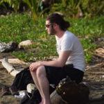 zach roz sitting on log beach