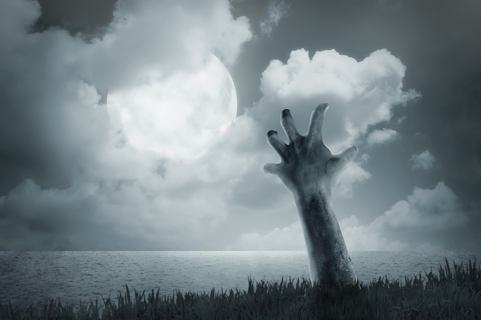 Zombie hand come out from ground in a spooky marsh