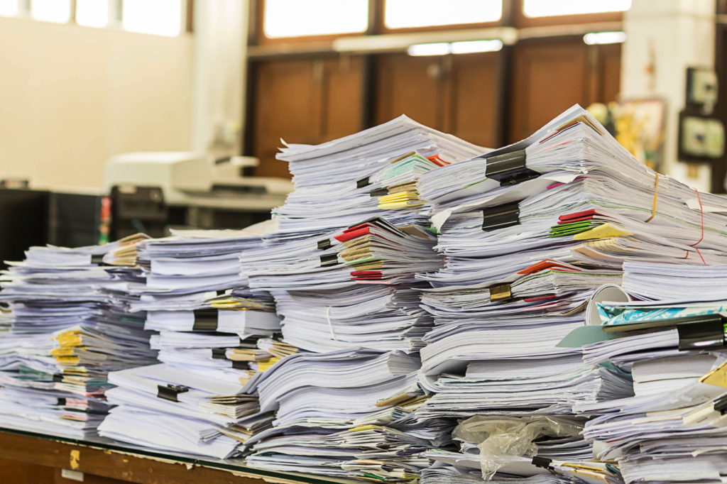 Stacks of paper with colorful clips in an office