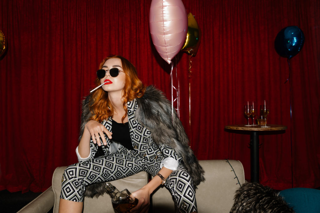 Chic redhead in sunglasses smoking a cigarette in a club alone with whiskey and balloons