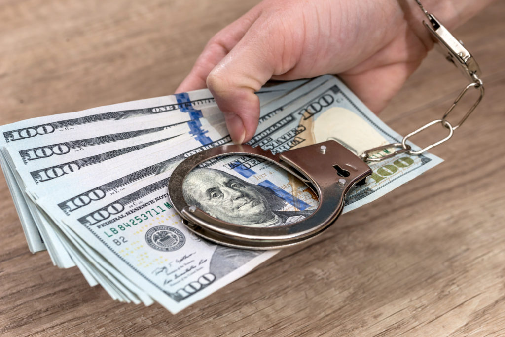 female hands in handcuffs with dollars on the table