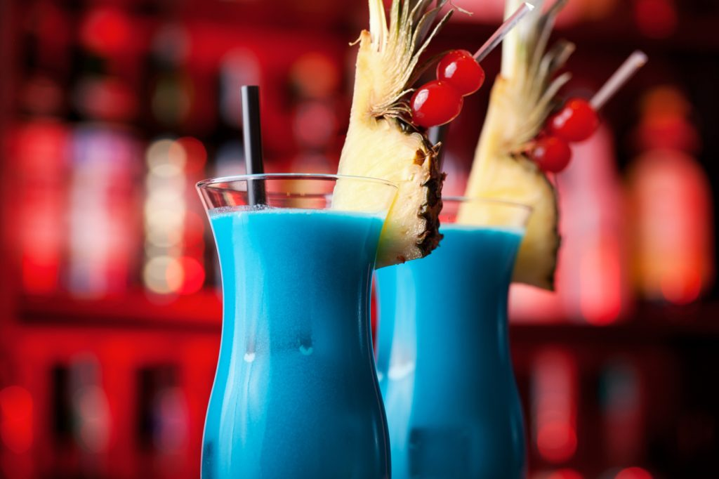 Two bright blue cocktails with fruit on a red background