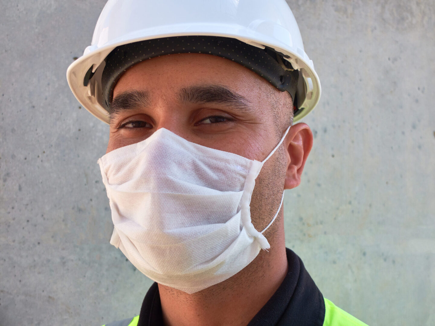 Civil,Engineer,Wears,Protective,Medical,Mask,Standing,Against,Concrete,Wall