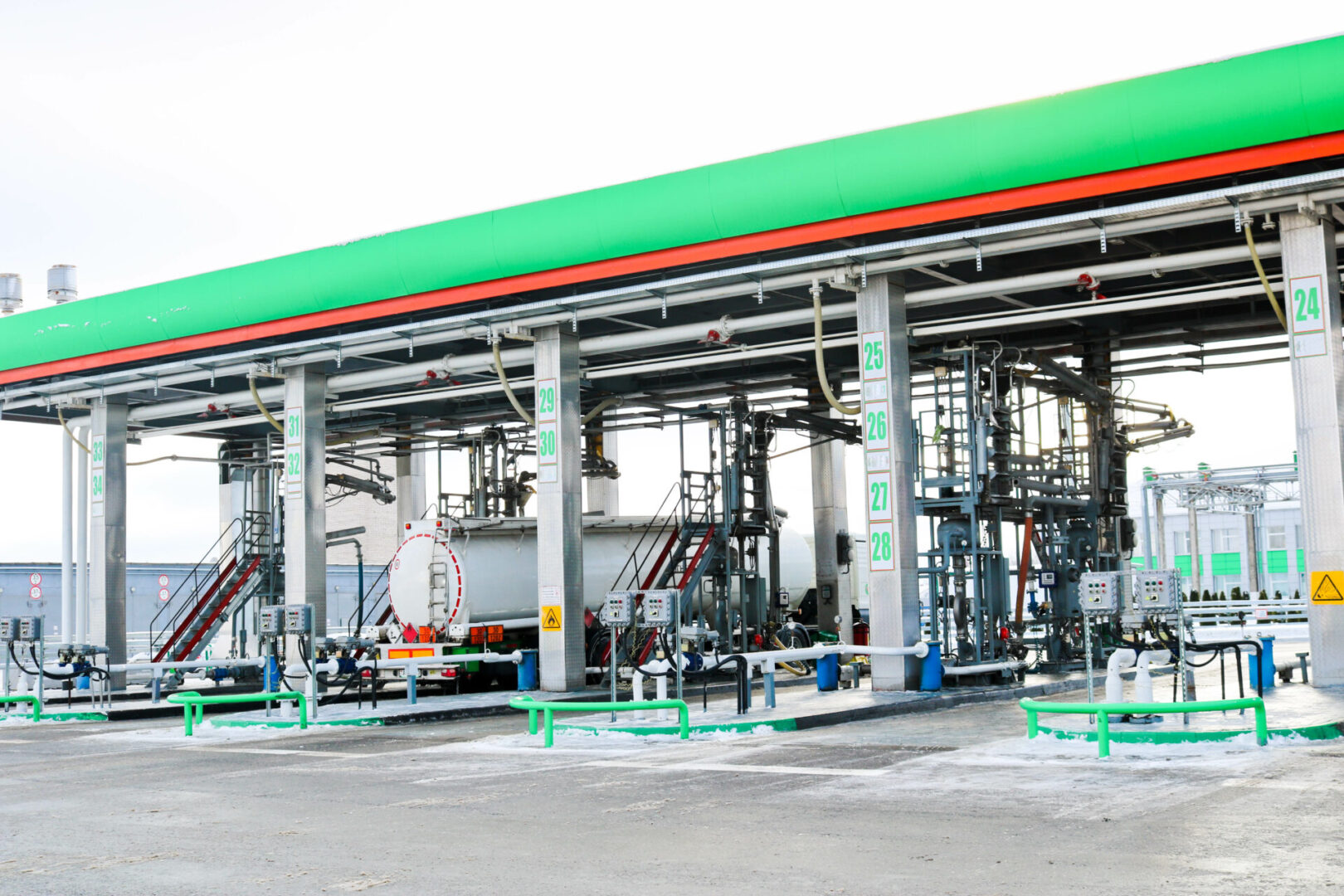 Large green industrial gas station for refueling vehicles, trucks and tanks with fuel, gasoline and diesel in the winter.