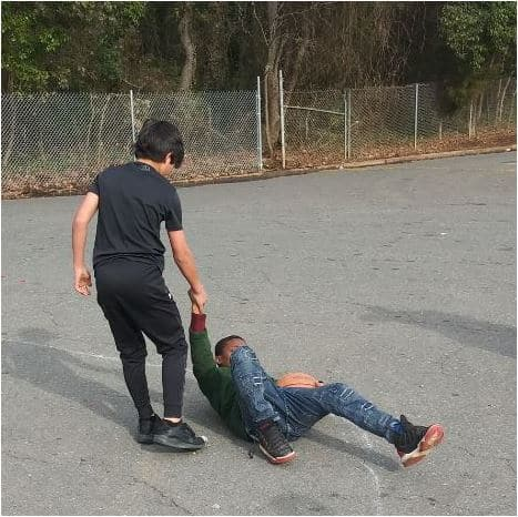Teenage boy helps a friend after playing sports together.