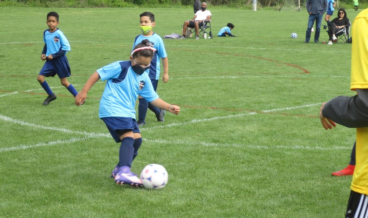 Girl soccer player kicking the ball.