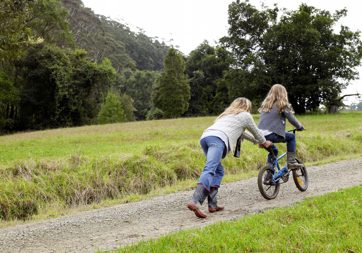Mother pushing daughter up hill on her bicycle