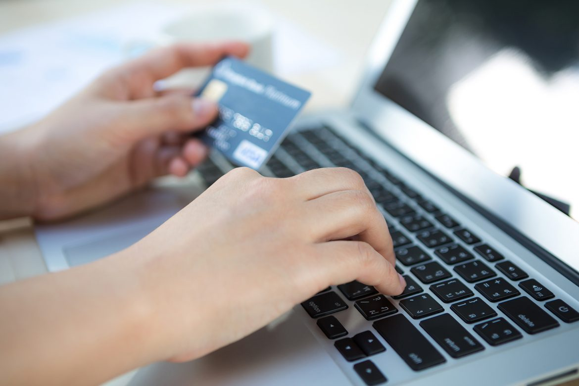 A person typing credit card information into their laptop