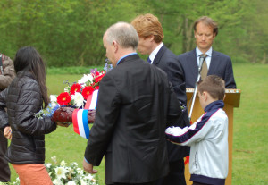 John Wilcock, U.S. Consul General laying wreath with local elementary school students.