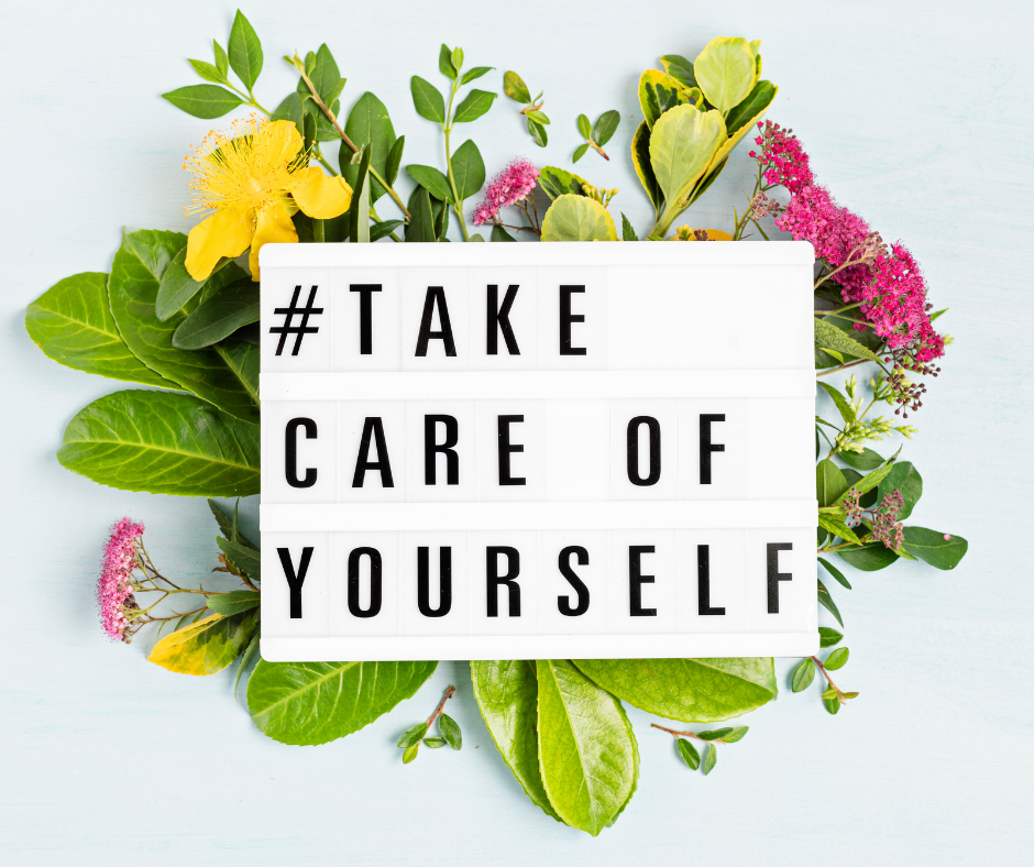 """Letter board that reads """"take care of yourself"""" on a bed of green leaves and flowers."""