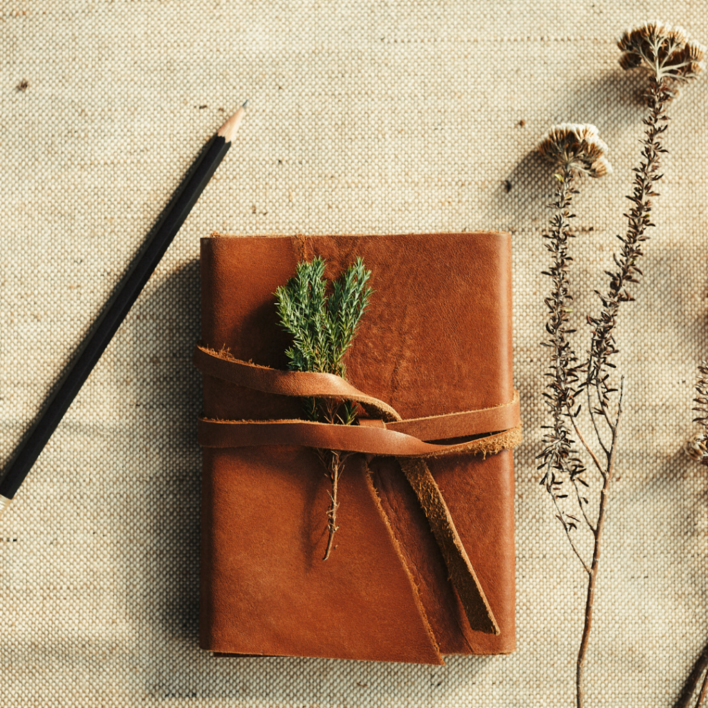 A leather journal on a linen cloth with a pencil and some dried plant stems nearby.