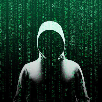 A faceless figure in a grey hoodie stands in front of a green pixelated background.