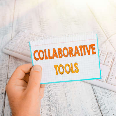 A white hand hold a white card with orange lettering that says 'collaborative tools.'