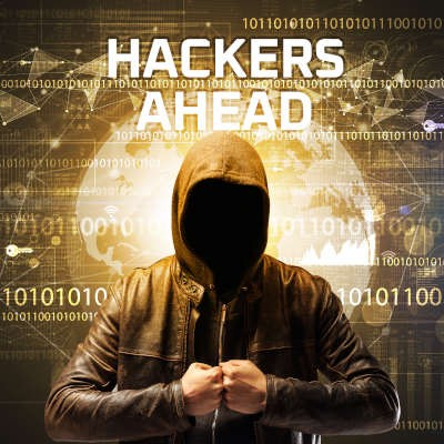 """A faceless man in a hoodie stands with his fists together and the screen behind him reads """"hackers ahead."""""""