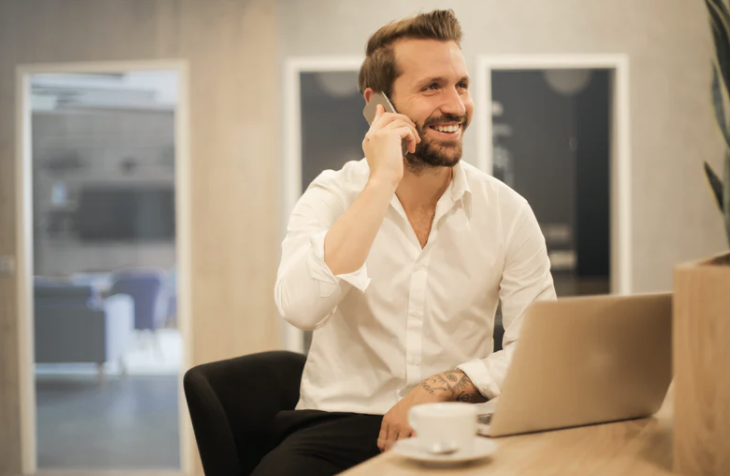 white male with a beard holding a phone to his ear sits at a desk with a laptop and cup of tea