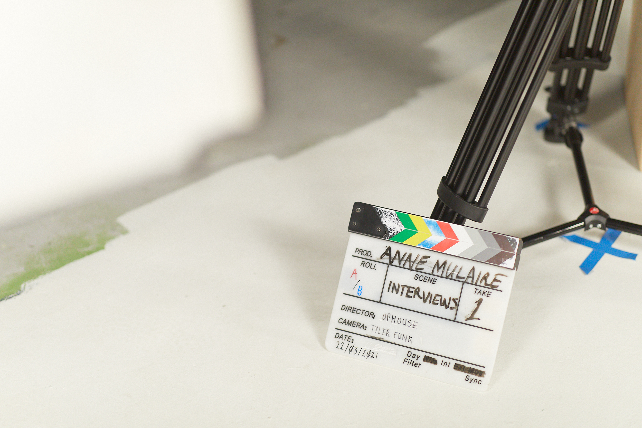 A film slate resting against a tripod