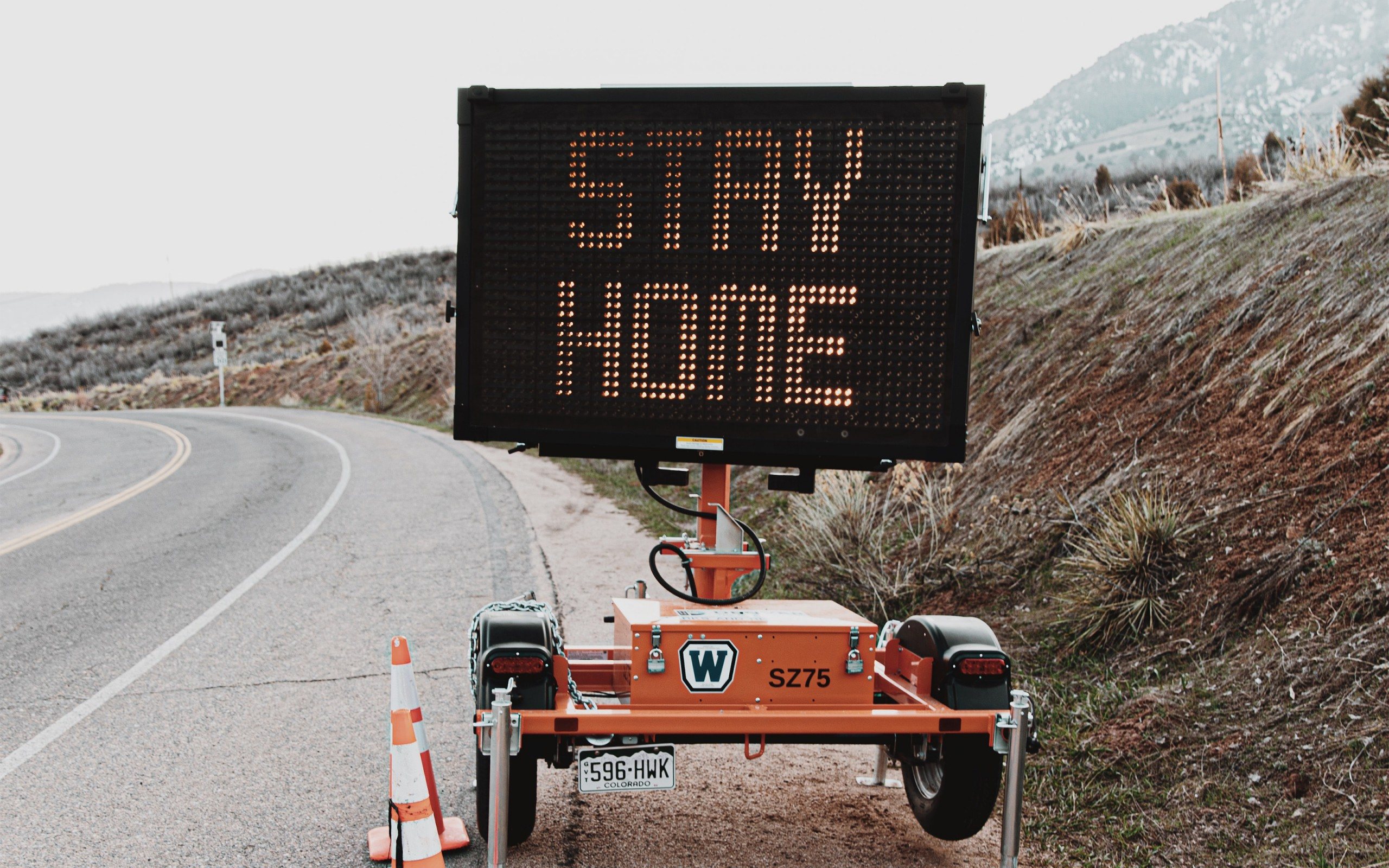 """Roadside electronic traffic sign displaying the message """"Stay Home"""""""