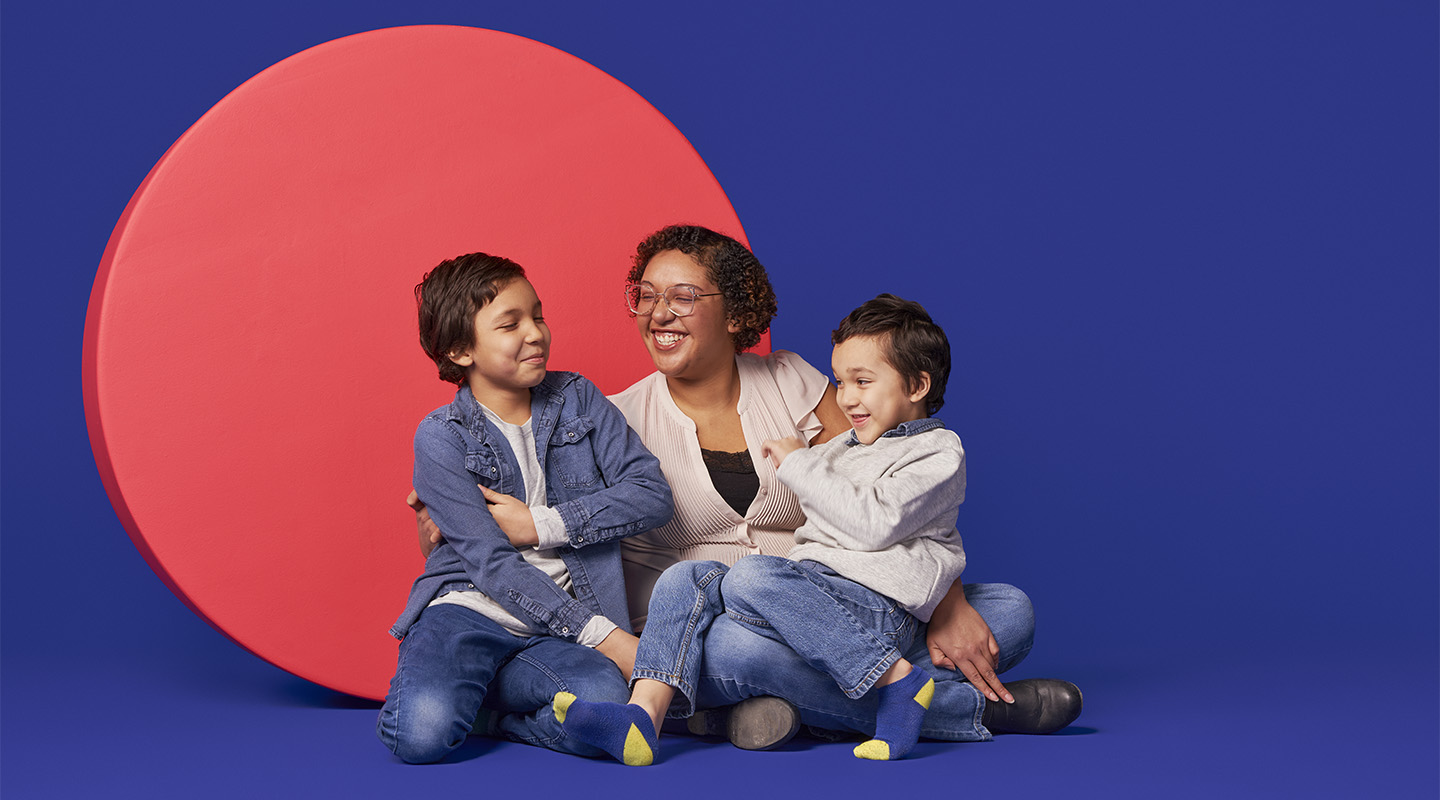 Still of a mother and two children against a pink circle and purple background.