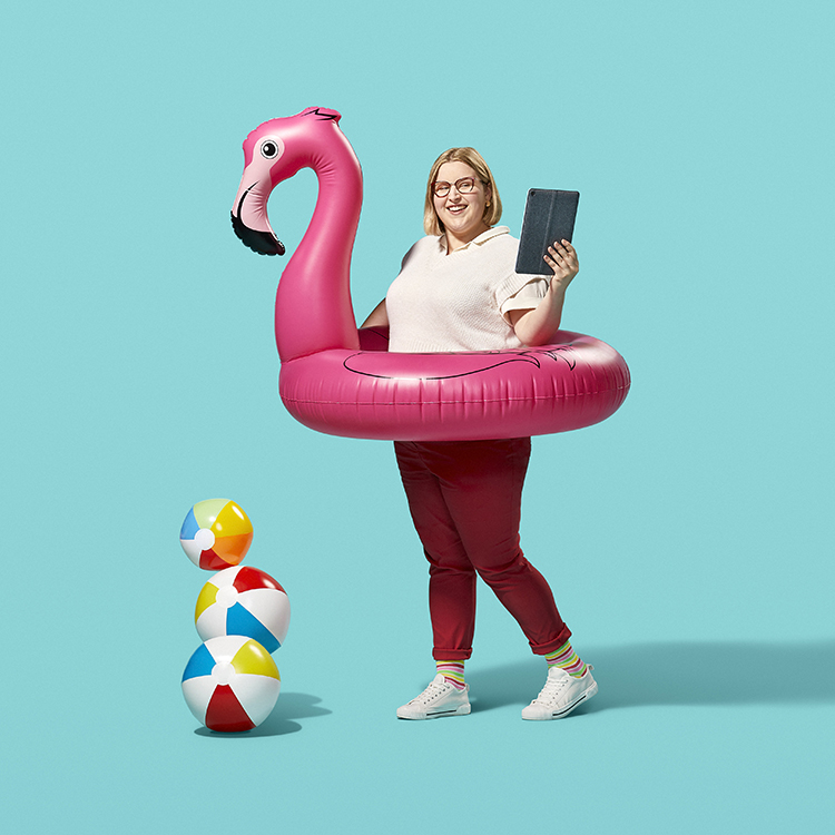 A Career Ready Student working on an iPad while inside of an inflatable flamingo inner tube,