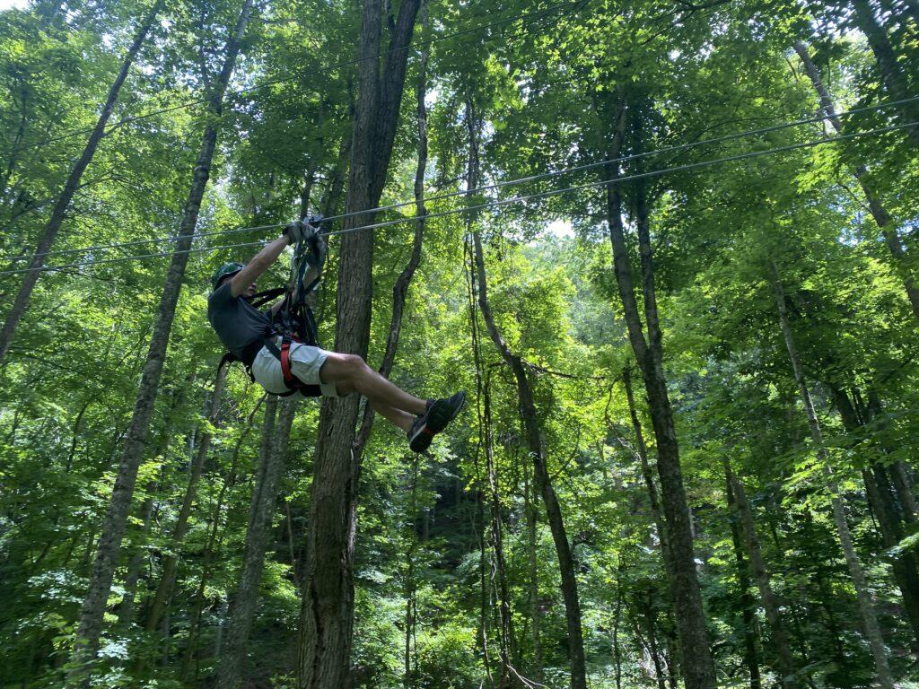 Man riding a zipline mid-zip.