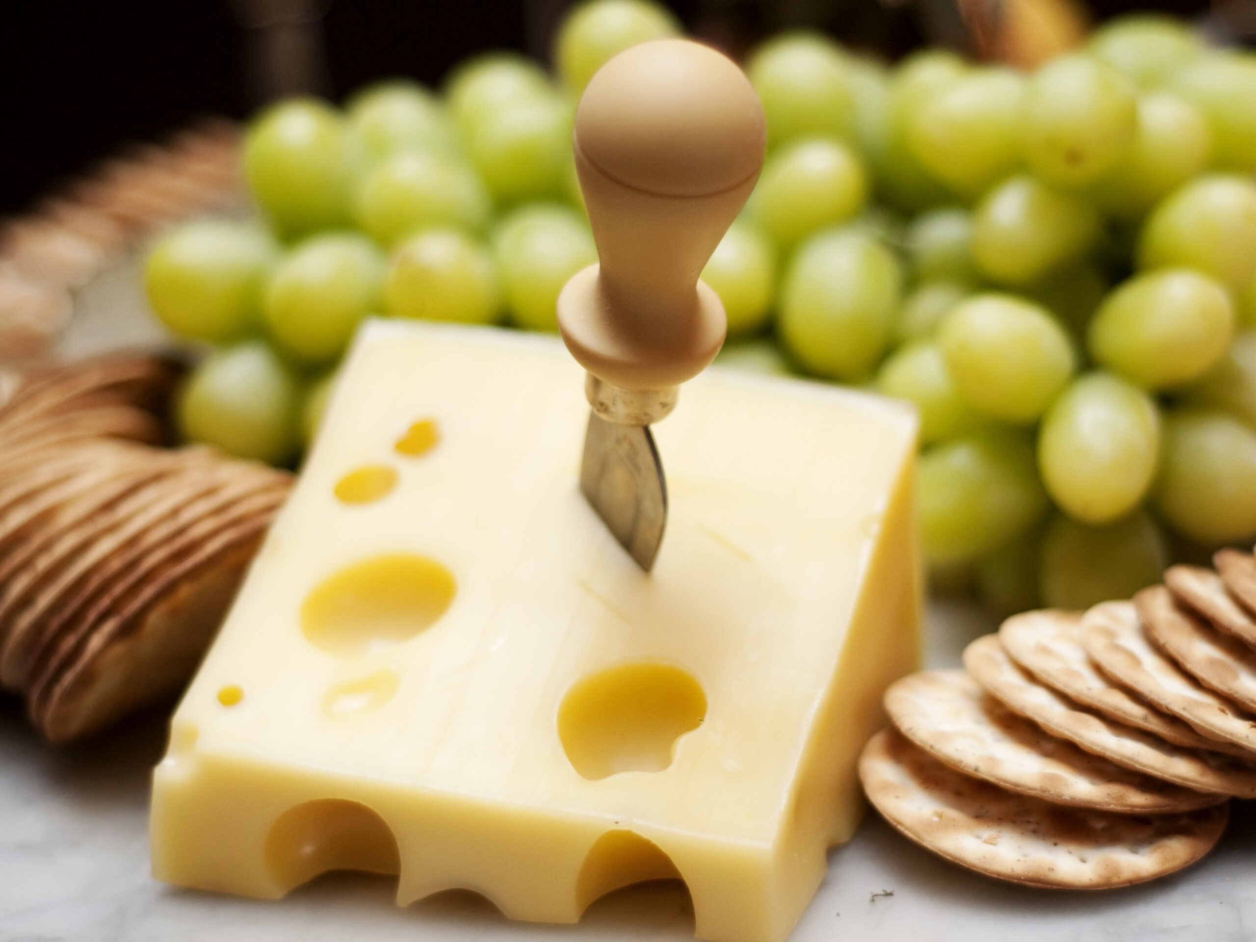 Cheese, crackers and green grapes spread on platter.