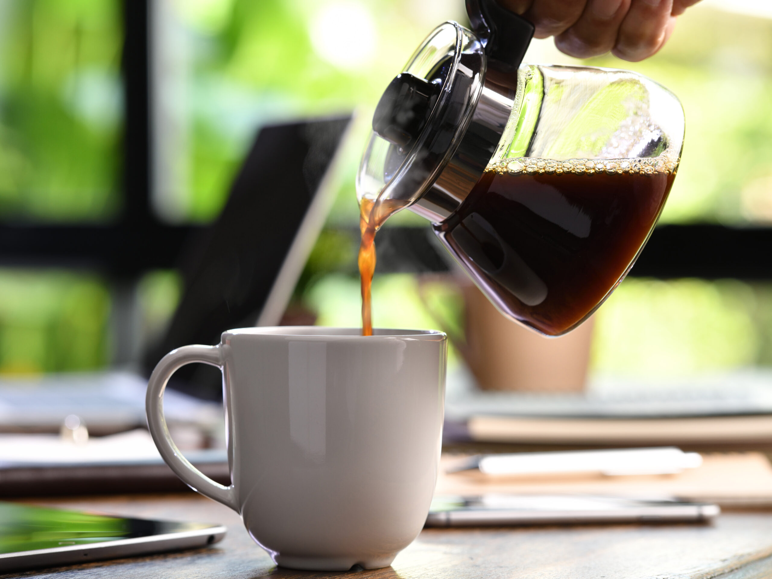 A hand pouring steaming coffee in to a cup on a work desk when work from home