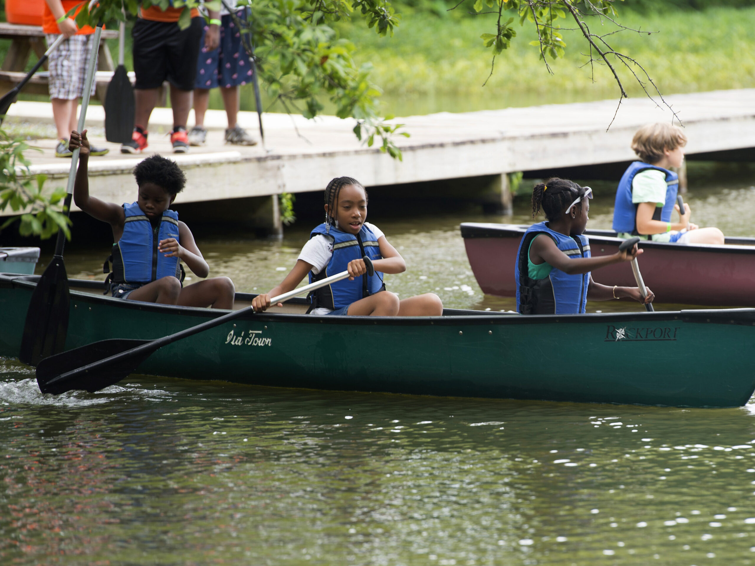 kids in canoes paddling away from the dock