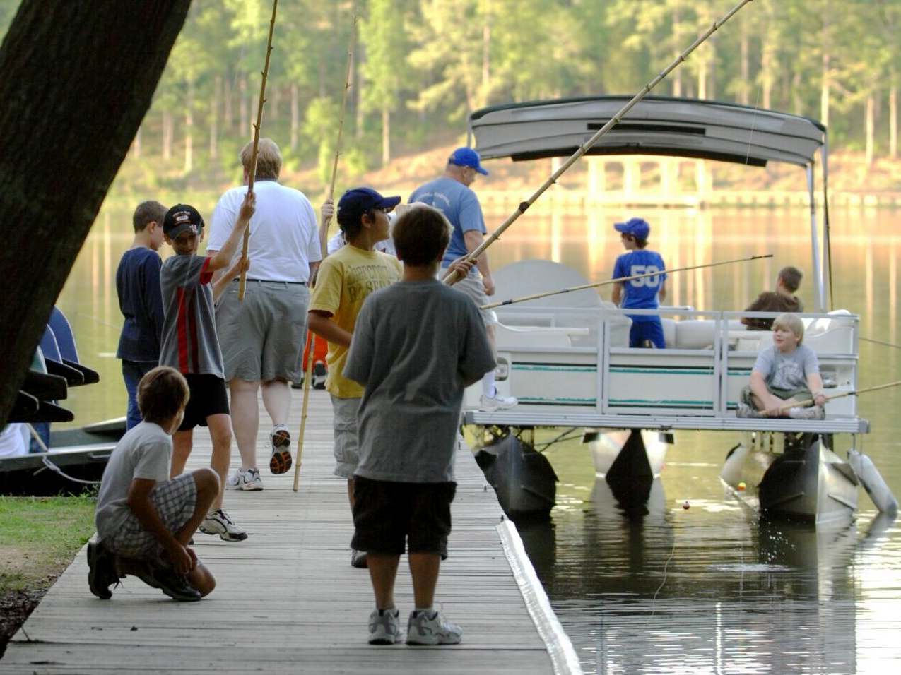kids prepare to go fishing on thepontoon boat with adults