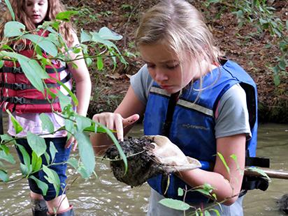 girls examining soil from the lake's edge.