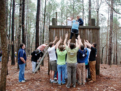 assisting a group member over the low ropes wall