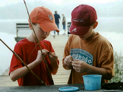 boys putting worms on the hooks of their fishing poles