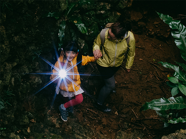 adult and child with a flashlight on a night hike