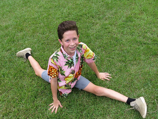 camper displaying the gymnastic talent of performing a split on the grass