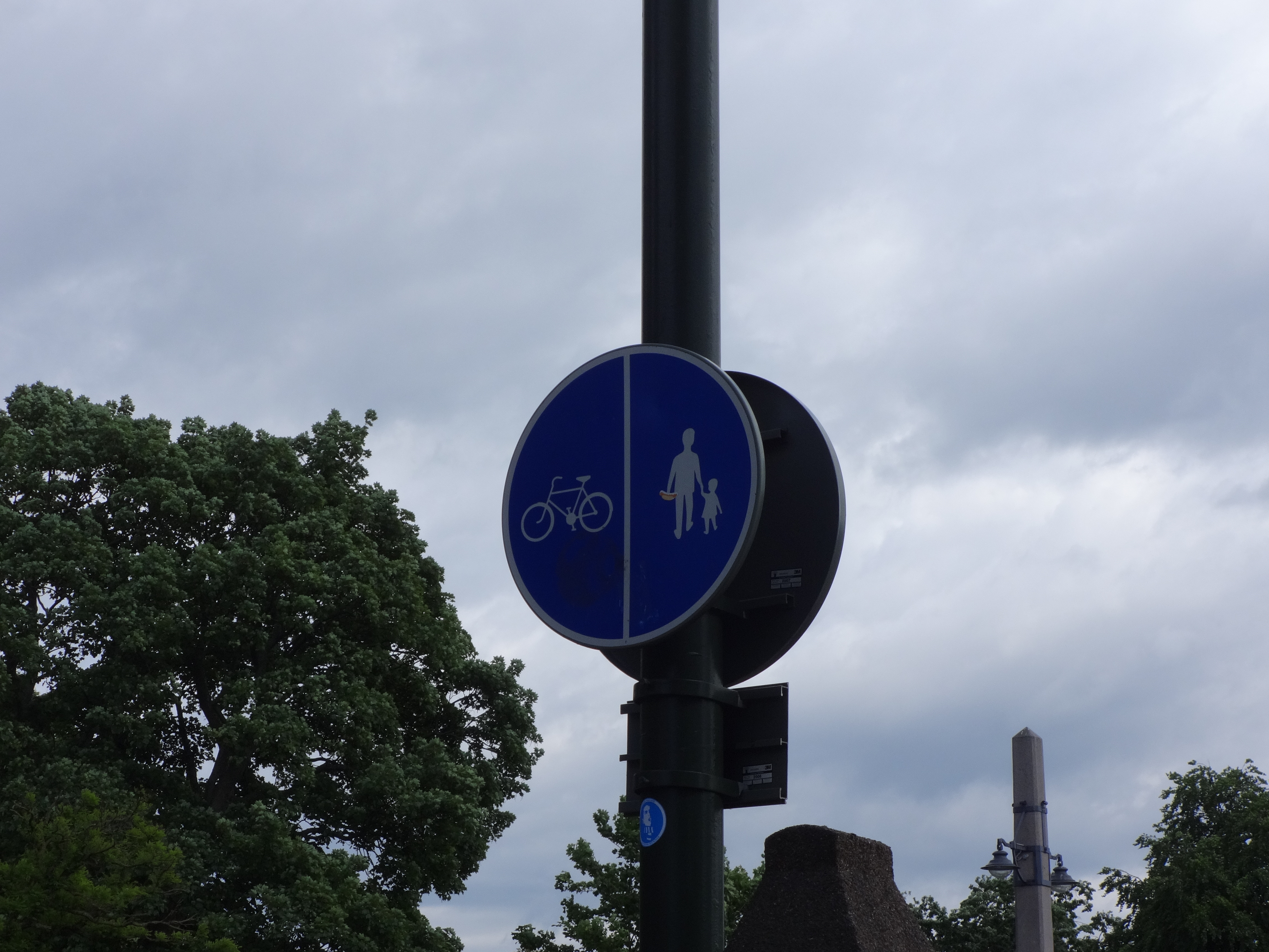 Sign signalling that bikes are on the left, pedestrians on the right (generally bikes would have smooth asphalt, while the pedestrians would have interlocking brick, etc.)