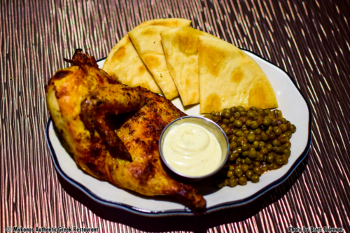 half roasted chicken, our amazing green peas, and pita bread