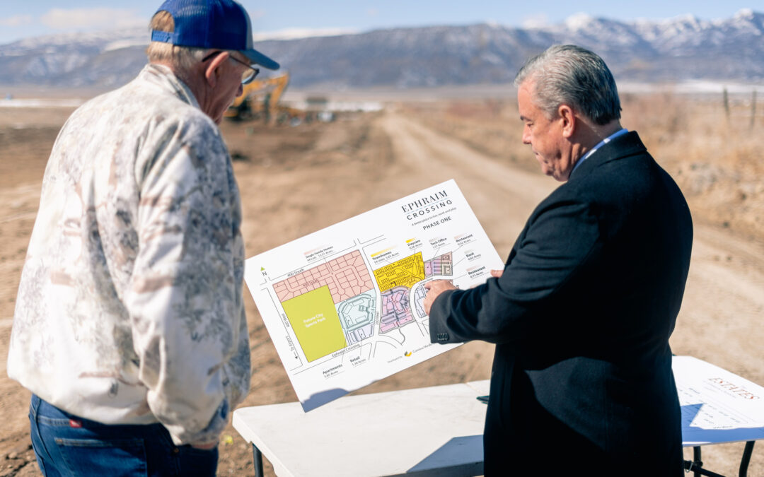 Miek Ballard of Camino Verde Group shows site map of Ephraim Crossing to groundbreaking attendee.